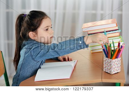 Little girl doing homework at the table in living room