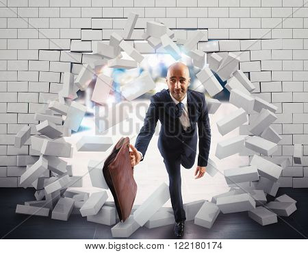Businessman with bag breaks through a wall