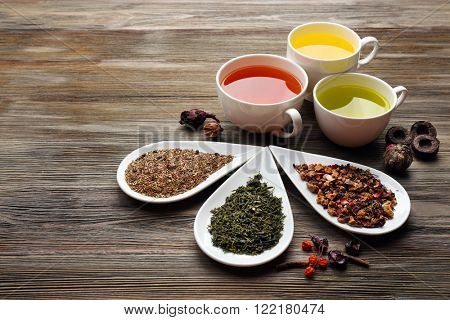 Tea concept. Different kinds of dry tea in ceramic bowls and cups of aromatic tea on wooden background