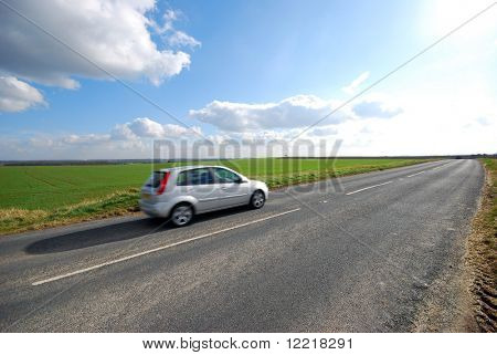 Car travels down Yorkshire country road in sunshine