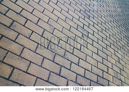 Full frame brick pavement close up from oblique low tilted angle in horizontal 3:2 format.