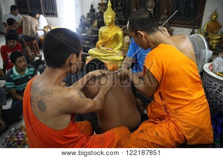 NAKHON CHAI, THAILAND - MAR 23, 2013: Buddhist monk makes traditional Yantra tattooing during Wai Kroo Master Day Ceremony in Wat Bang Pra on Mar 23, 2013 in Nakhon Chai, Thailand.