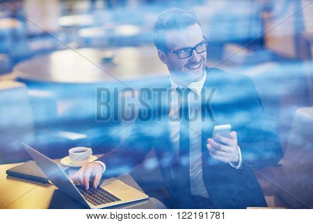 Young smiling businessman sitting at café with laptop and smartphone