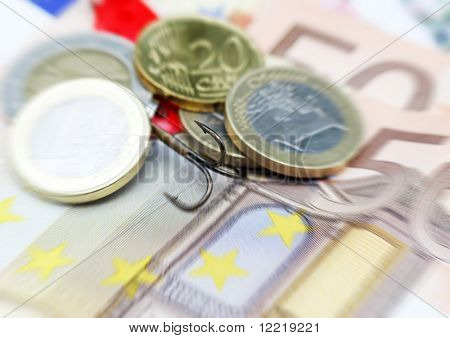 Close-up of fishing hook hidden in Euro currency