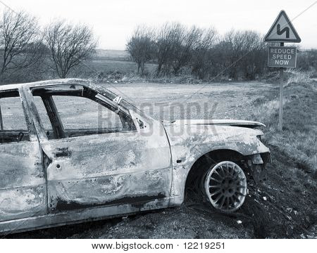 Burnt out abandoned car on side of road