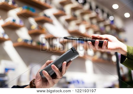 Woman paying with NFC technology on smart phone