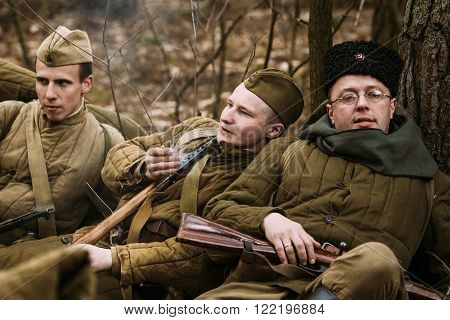 PRIBOR, BELARUS - April, 04, 2015: Group of unidentified re-enactors dressed as World War II Soviet russian soldiers in overcoat resting in forest
