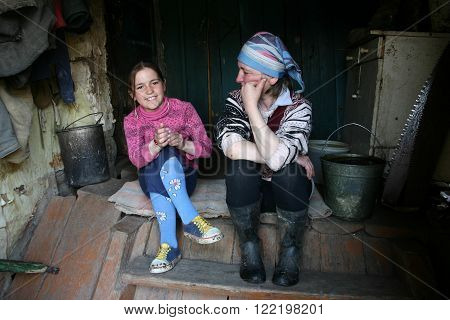 Lipovec village Tver region Russia - May 2 2006: Mature woman talking with a girl 11 years old sitting on the steps of the farmhouse.