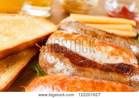 Oktoberfest traditional menu beer and roast beef or chicken sausage with ketchup mustard and rosemary. Wooden background ** Note: Shallow depth of field