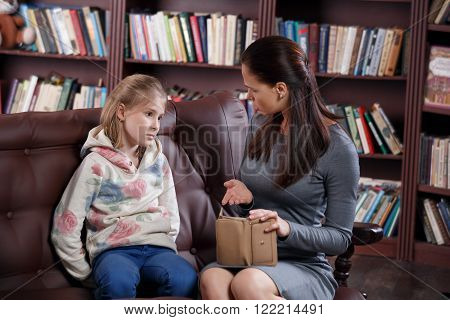 Strict young mother scolding little girl about money