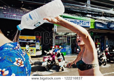 KO SAMUI, THAILAND - APRIL 13:  Unidentified woman pouring ice water by the collar on Songkran Festival (Thai New Year) on April 13, 2014 in Chaweng Main Road, Ko Samui island, Thailand.