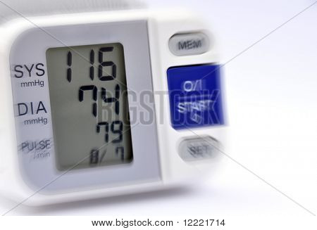 Closeup of blood pressure monitor showing recent reading