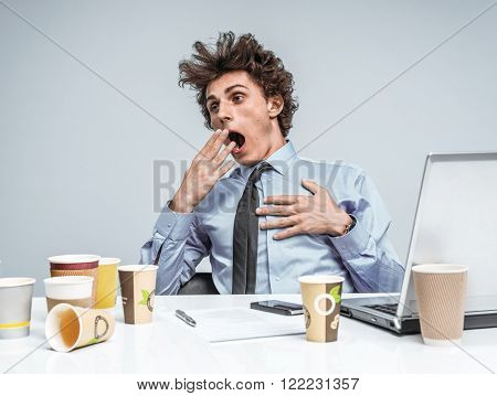 Sleepy exhausted or bored young businessman in yawn. An exhausted or bored manager yawning with his hand to his wide open mouth and apathetic eyes