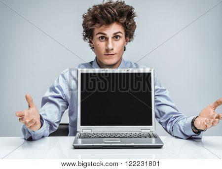 Young manager threw up his hands and in disbelief. Modern businessman at the workplace working with computer. Business concept