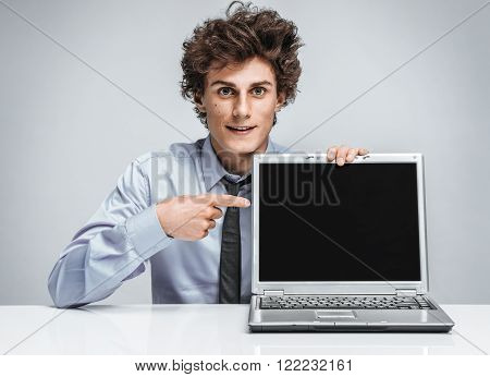 Young salesman showing at screen laptop / modern businessman at the workplace working with computer