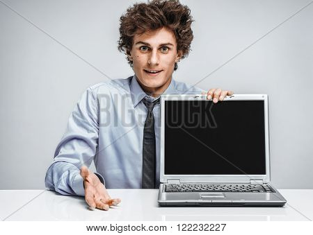 Young man shows presentation on laptop. Modern businessman at the workplace working with computer. Business concept