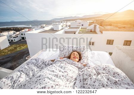 Young and cute woman sleeping on the bed on the roof top with white houses on the background. Concept of dreaming during the sleep.