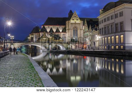 Quay Graslei, picturesque medieval St Michael's Bridge and church at night in Ghent, Belgium