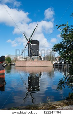 Dutch windmill reflecting in the river Rijn Leiden Netherlands