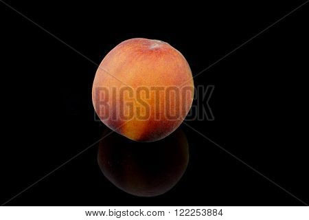 a whole peach on a black background