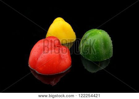 three half paprika in different colors on black
