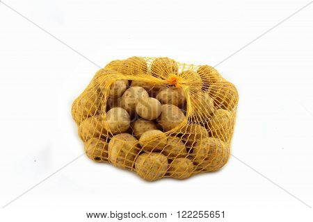Potatoes in the bag yellow mesh on white background