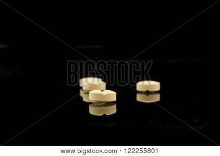 four yellow tablets on a black background