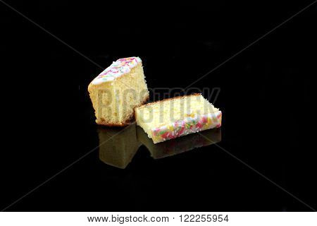 two lemon cake pieces on black background