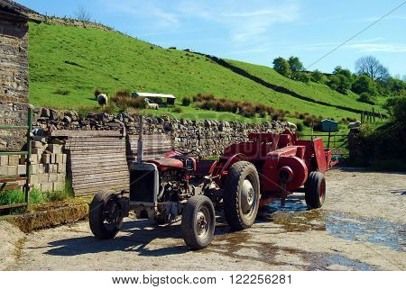 Old tractor is parked in farmyard with sheep on hill in background
