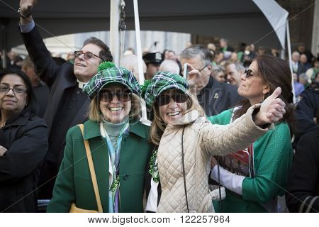 NEW YORK - MARCH 17, 2016: Parade goers watch from the sidewalk in front of St Patricks Cathedral during the parade on Saint Patricks Day in Manhattan on March 17, 2016.