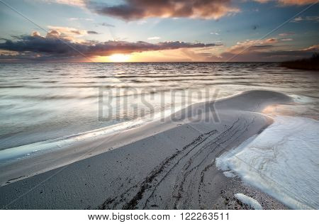 sundown during low tide on Ijsselmeer lake Hindeloopen Netherlands