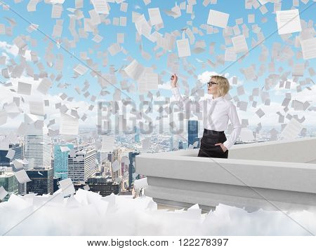 Businesswoman standing on roof throwing paper plane Paris view papers flying around. Blue sky at background. Concept of starting new project.