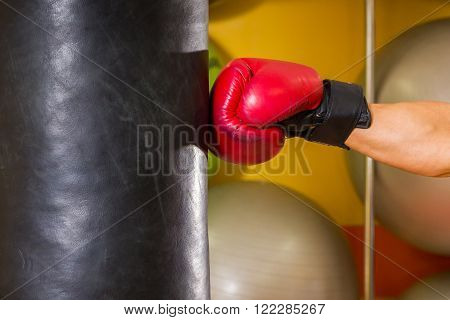Muscular man in the gym. The man in boxing gloves, hit a punching bag, exercise. Boxing, workout, muscle, strength, power - the concept of strength training and boxing