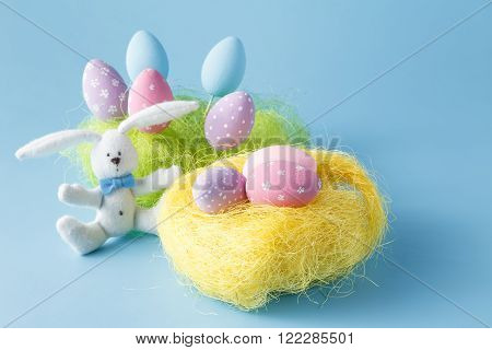 Homemade Hand Painted Easter Eggs of Various Colors in a Nest on blue Background