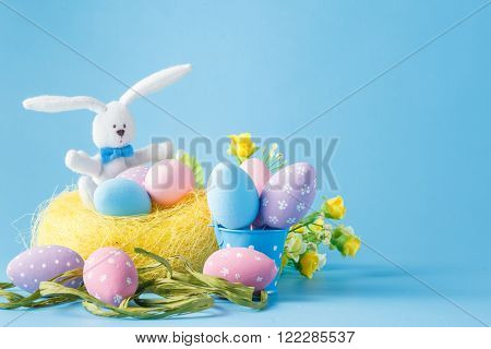 Colored Easter egg decorations over blue background