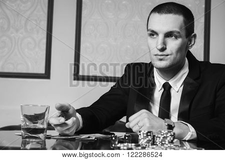 Poker player. Young guy in the casino at the gaming table. Man gambling, card games. Cards, chips, whiskey, cigarettes, poker, card game, gambling - gambling concept.