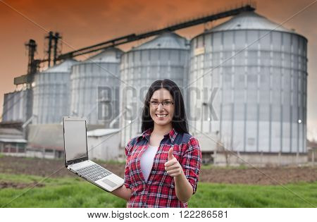 Girl With Laptop In Front Of Silo