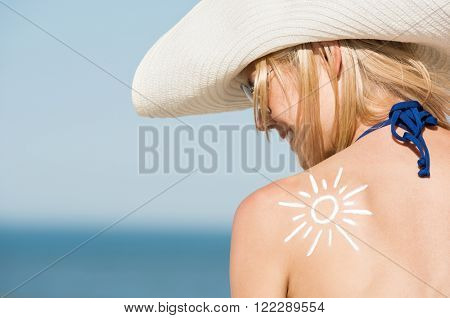 Close up of shoulder of beautiful woman with a sun drawn with the suntan lotion. Back pose of girl wearing hat and sunglasses at beach. Beautiful woman sunbathing with a sunscreen lotion on shoulder.