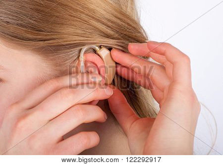 Close up of a woman's ear with hearing aid.