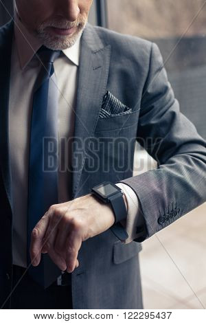 I am very busy. Senior businessman is looking at his smart watch with anticipation. He is standing near the window