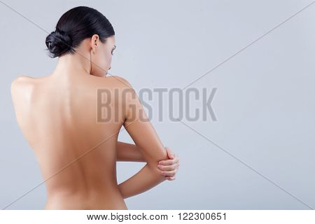 Cute young slim girl is making massage of her arm. She has pain in elbow. Focus on her back. Isolated and copy space in right side