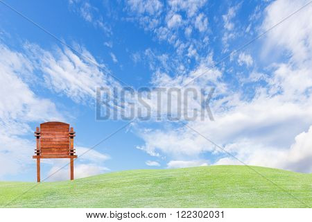 Guide wooden post on green field and sky