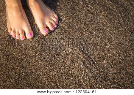 Shy Girl Feet Standing In Sand.a Wave comes in, as I stand and wait. copy space. top down view.Naked feet at the Beach - Barefeet nature Background.