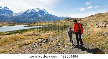 panorama of family of two, father and son, enjoying hiking in torres del paine national park, patagonia, chile