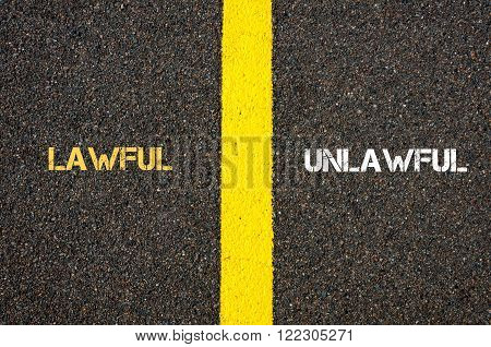 Antonym concept of LAWFUL versus UNLAWFUL written over tarmac, road marking yellow paint separating line between words