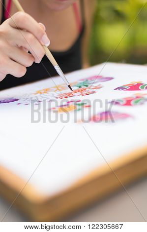PHUKET, THAILAND - May 24 2015 : Unidentified tourist woman use watercolor to color on the fabric to make Batik in Batik free training course.