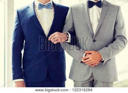people, homosexuality, same-sex marriage and love concept - close up of happy male gay couple holding hands on wedding