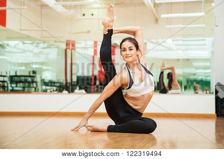 Flexible Young Woman Doing A Leg Split At The Gym