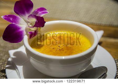 Creme Brulee dessert close up served with a flower