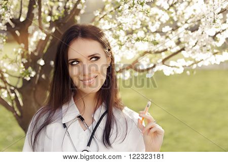 Spring Woman Doctor Smiling and Holding Vaccine Syringe Portrait of female medical professional with allergy immunization remedy  in springtime